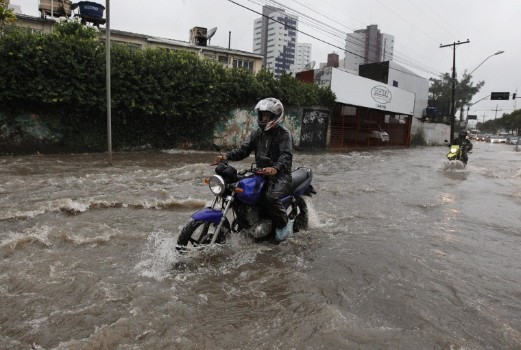 Image: Motorcyclists make their way down a flooded street after heavy rain storms in Recife, Brazil, on Thursday