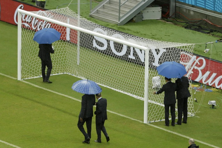 Image: Referees check out the goal prior to the group G World Cup soccer match between the USA and Germany on Thursday.