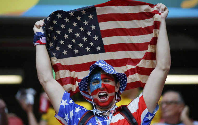 A fan of the U.S. cheers while holding the national flag before their 2014 World Cup Group G soccer match against Germany at the Pernambuco arena in Recife June 26, 2014. REUTERS/Laszlo Balogh (BRAZIL  - Tags: SOCCER SPORT WORLD CUP)