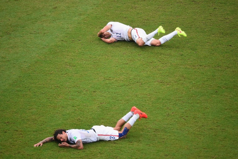 Jermaine Jones of the United States and teammate Alejandro Bedoya lie on the field after colliding during the 2014 FIFA World Cup Brazil group G match between the United States and Germany at Arena Pernambuco on June 26 in Recife, Brazil.
