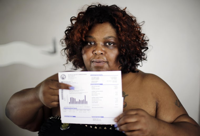 Image: Nicole Hill holds up her past due water bill at her home in Detroit