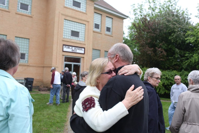 Image: Former members of the Cyrus elementary school community embrace during a reunion at the school in Cyrus, Minn.