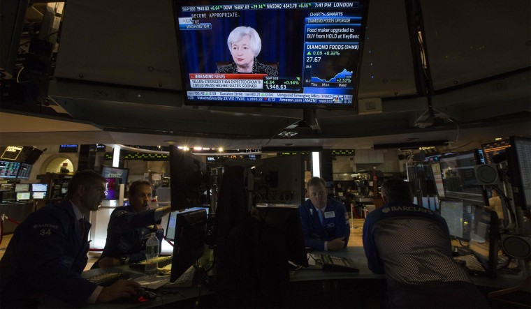 Image: Television screen displays Federal Reserve Chair Yellen's news conference as traders work on the floor of the New York Stock Exchange