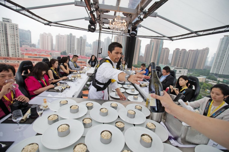 Image: A chef serves diners at a table lifted 50 meters above the ground in Shanghai.