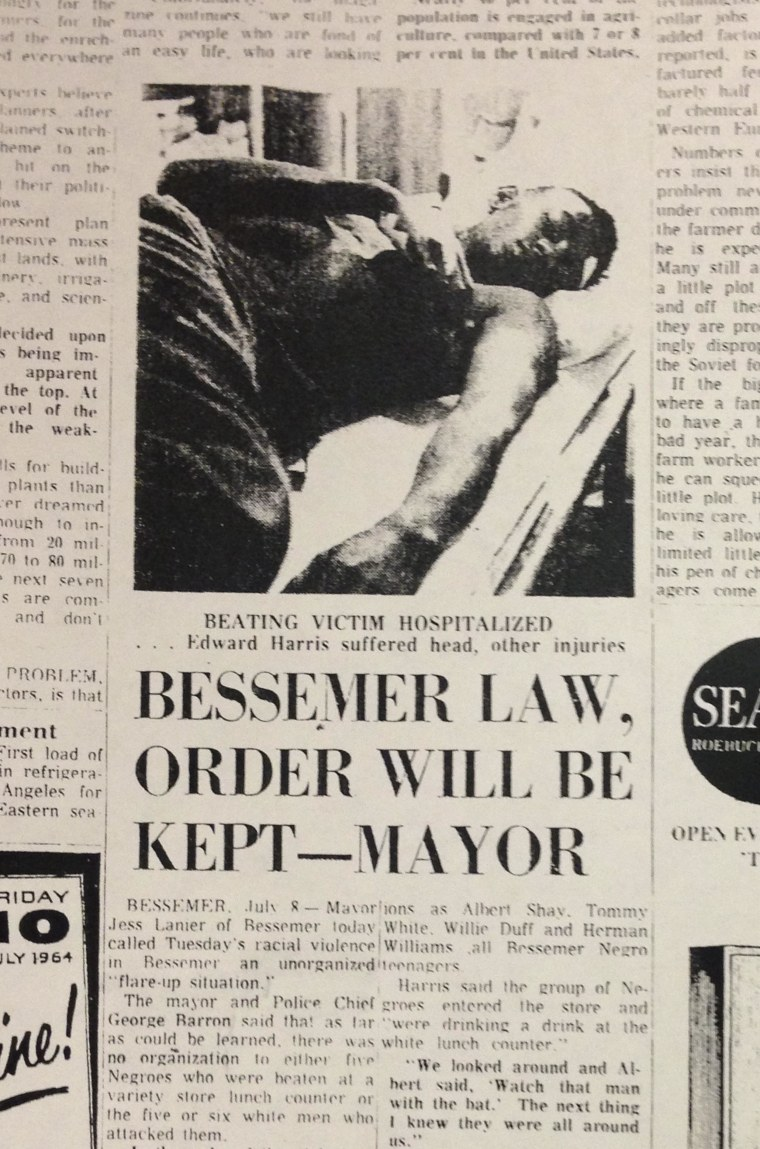 """Image: A newspaper clipping from 1964 featured a headline proclaiming, """"Bessemer Law, Order will be Kept - Mayor,"""" and a photo of Edward Harris, who was beaten during a sit-in at McLellan's department store."""