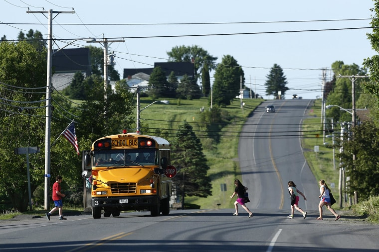 Image: Students run to school on Rte. 1 on their way to the Wellington public school in Monticello, Maine, on June 16.