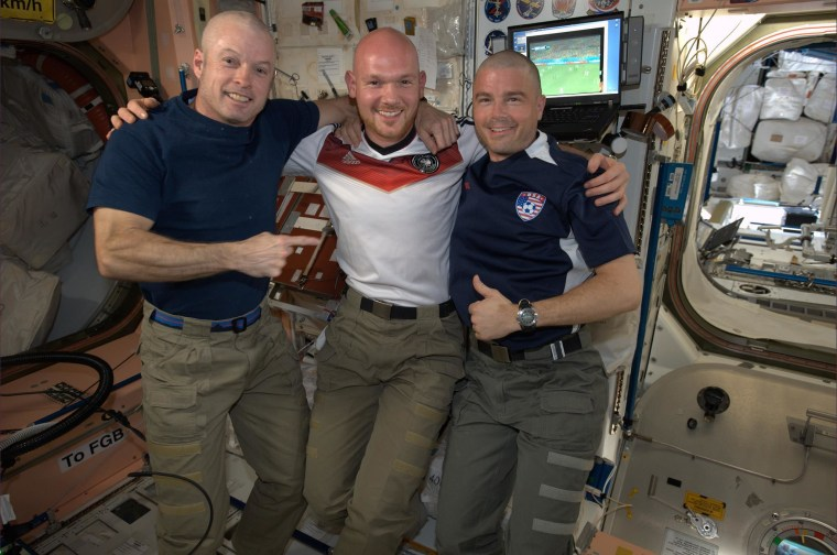 U.S. astronauts Steve Swanson and Reid Wiseman, right, show off their freshly-shaven heads after Gerst shaved them aboard the International Space Station