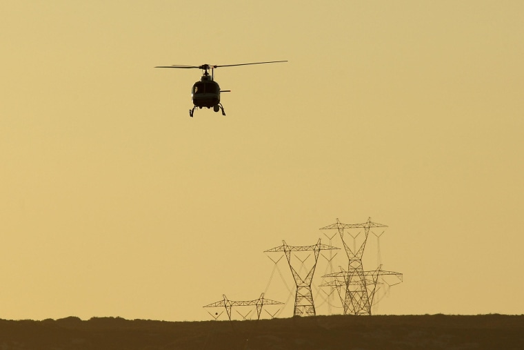 Image: A helicopter patrols as agents carry out special operations near the US-Mexico border fence