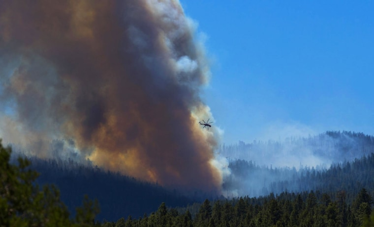 A helicopter battles the blaze with lake water as smoke rises from the trees of the San Juan fire near Vernon, Az., on June 27. Authorities say communities mostly populated with summer homes are under mandatory evacuation orders as of Thursday evening due to the growing wildfire.