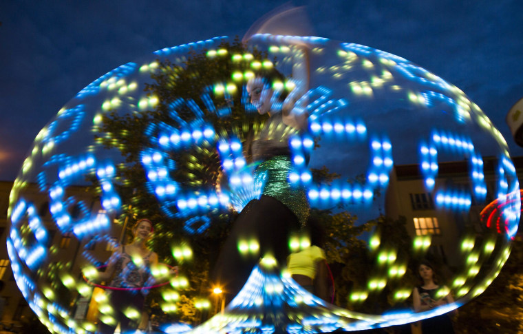 Image: A hooper performs with an illuminated hula hoop at the Hula Hoop Festival Hoopurbia