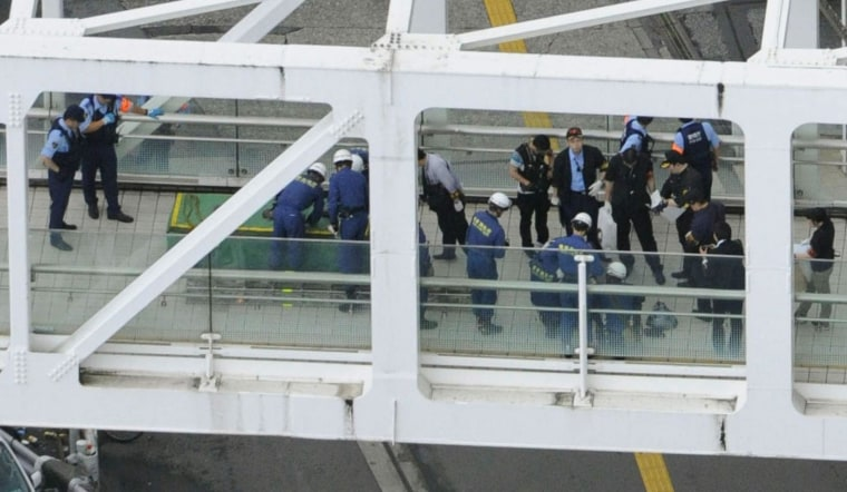 Image: Police officers and fire-fighters investigate the site where a man set himself on fire at a pedestrian walkway near Shinjuku station in Tokyo