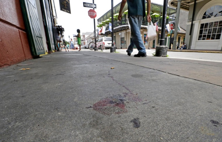 Image: Blood stains are seen on the sidewalk at the scene of a shooting