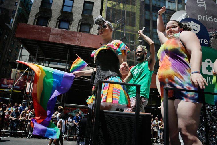 Image: People on a float dance and wave flags during the Gay Pride Parade