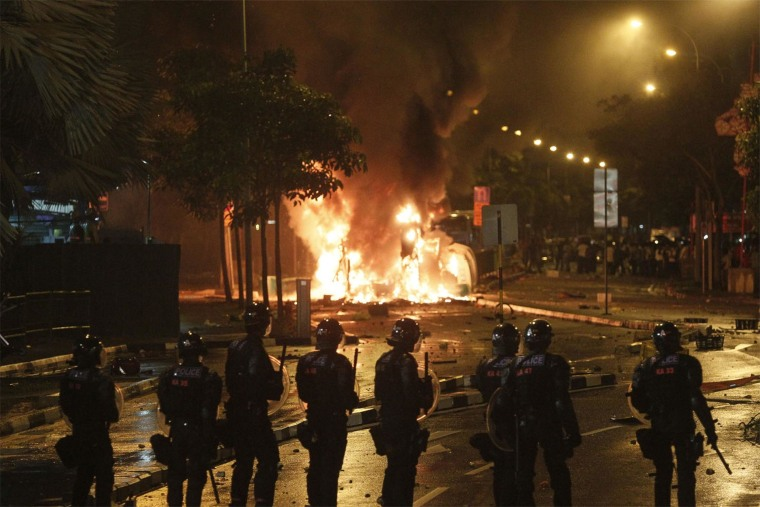 Image: Riot police stand guard near a burning vehicle on Dec. 8, 2013