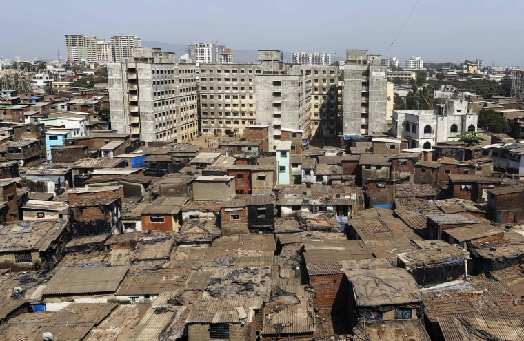 Image: High-rise residential buildings are seen behind a cluster of houses at a slum in Mumbai