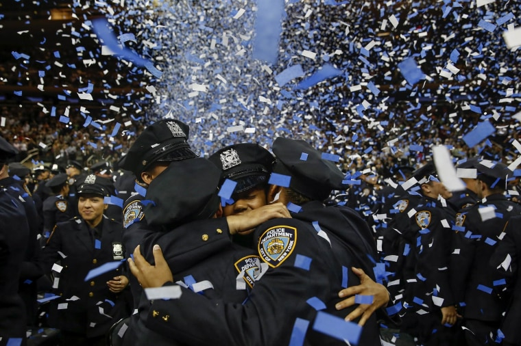 Image: Members of the June 2014 graduating class of the New York City Police Academy embrace during their graduation ceremony at Madison Square Garden in New York