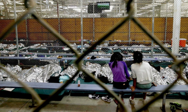 Image: Two young girls sit in their holding area at a U.S. Customs and Border Protection placementer center in Arizona.