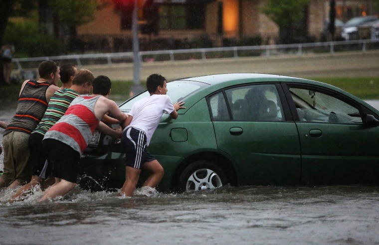 Image: People push a vehicle that stalled at a flooded intersection in Madison.