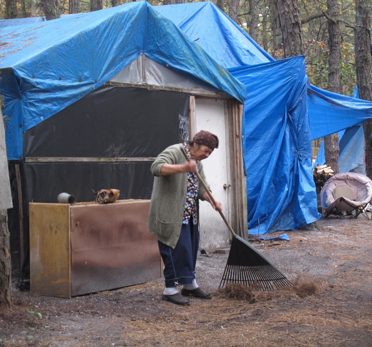 Image: A resident of the Tent City encampment of homeless people in the woods of Lakewood, N.J., rakes the dirt in front of her tent in 2012.