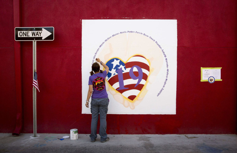 Image: Artist Jenn Winters paints a mural in memory of the 19 Granite Mountain Hotshot Crew firefighters who died while fighting the Yarnell Hill Fire