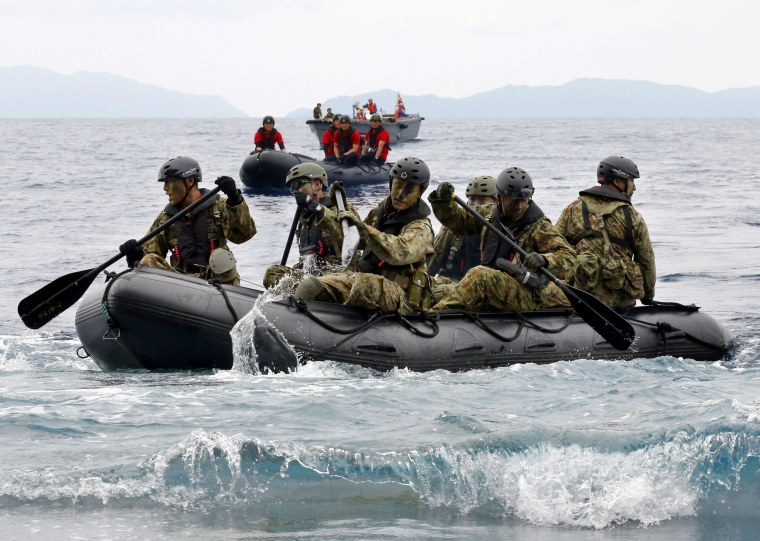 Image: JSDF soldiers approach Eniyabanare Island from JSDF transport vessel Shimokita during a military drill, off Setouchi town on the southern Japanese island of Amami Oshima
