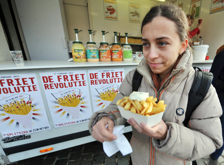 """Image: A woman eats French fries (fried chips) with mayonnaise on the \""""Chips Revolution\"""" Day\"""" in Leuven"""