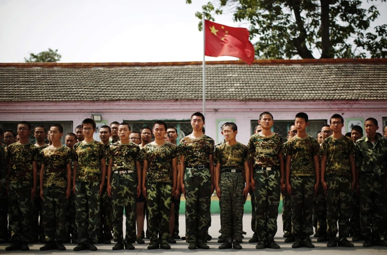 Image: Students stand in front of the Chinese national flag as they prepare to take part in a military drill at the Qide Education Center in Beijing