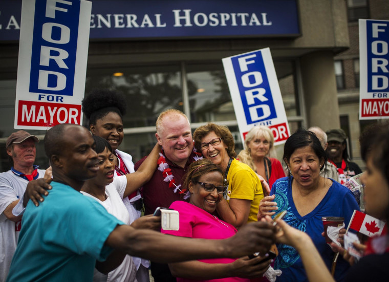 Toronto Mayor Rob Ford poses with members of the public as he takes part in the East York Canada Day Parade in his first public appearance since returning from a rehabilitation clinic for substance abuse problems in Toronto on July 1.