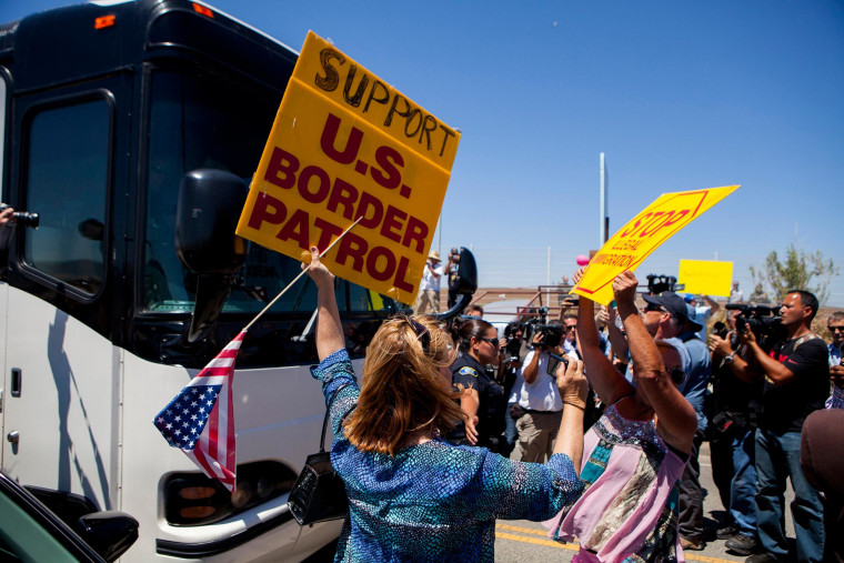 Image: Demonstrators picketing against the arrival of undocumented migrants who were scheduled to be processed at the Murrieta Border Patrol Station block the buses carrying the migrants in California