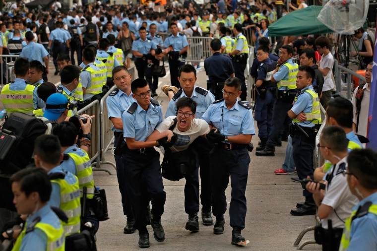 Image: A protester is taken away by police officers after hundreds of protesters staged a peaceful sit-in overnight in Hong Kong