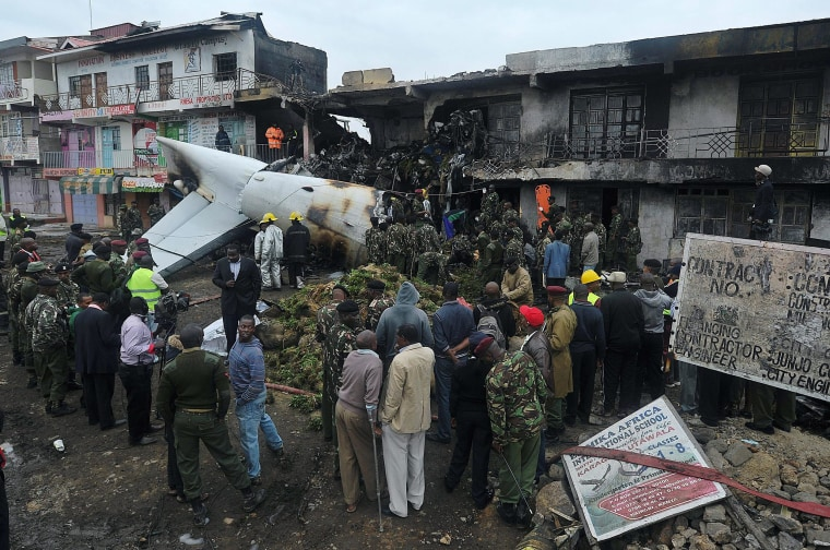 Image: Rescuers and onlookers look at the wreckage of a cargo plane