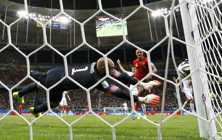 Image: Goalkeeper Howard of the U.S. blocks a shot from Belgium's Kompany during their 2014 World Cup round of 16 game at the Fonte Nova arena in Salvador