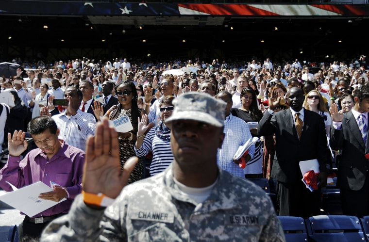 Image: More than 1,000 citizenship candidates raise their hands for the Oath of Allegiance during a naturalization ceremony at Turner Field