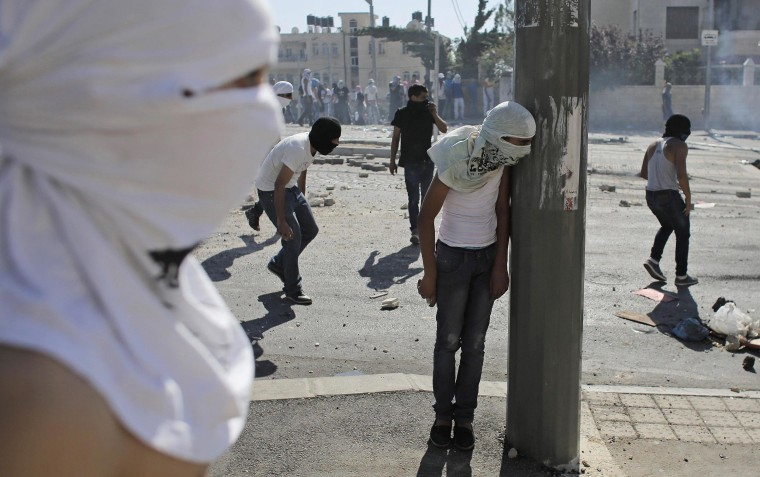 Image: A Palestinian stone-thrower takes cover behind a street pole during clashes with Israeli police in Shuafat