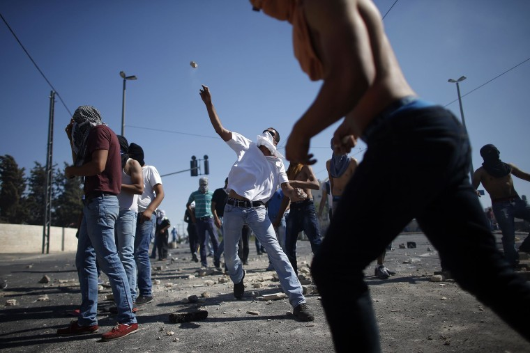 Masked Palestinian protesters throw stones towards Israeli police during clashes in the Shuafat neighborhood in Israeli-annexed Arab East Jerusalem, on Thursday, one day after a Palestinian teenager was kidnapped and killed in an apparent act of revenge for the murder by militants of three Israeli youths.