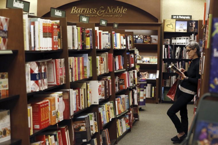 Image: File of a woman reading a book at a Barnes & Noble bookstore in Pasadena, California