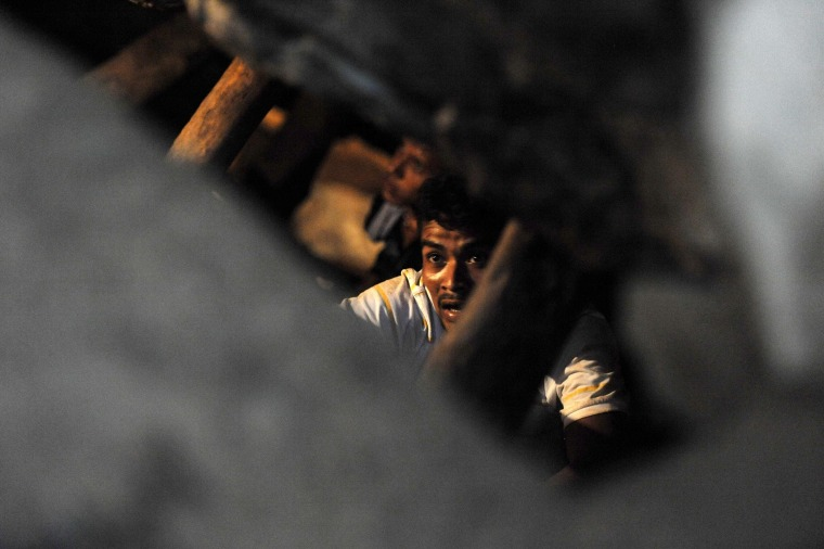 Image: Men make their way inside the collapsed San Juan mine, i