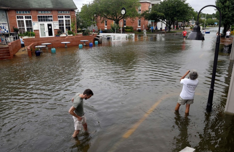 People walk along a flooded street near the waterfront in Manteo, N.C., July 4, 2014, after Hurricane Arthur passed through the area leaving some roads underwater.