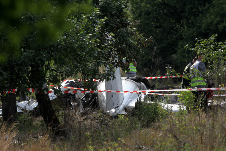 Police officers inspect the plane wreck at the crash site in Topolow, near Czestochowa, southern Poland, 05 July 2014. Eleven people died and one was severely injured when the Piper PA-31 Navajo plane crashed and caught fire. The aircraft, which had taken off only a few minutes earlier from a nearby airfield, apparently carried parachutists, officials said.