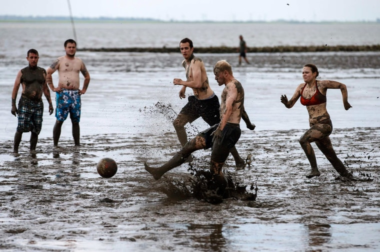 Image: Players fight for the ball during a soccer match at the Mud Olympics in Brunsbuettel