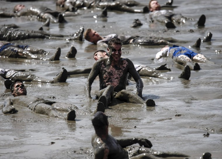 Image: A participant smiles during attempt to break world record for total number of 'mud angels' at the Mud Olympics, in Brunsbuettel