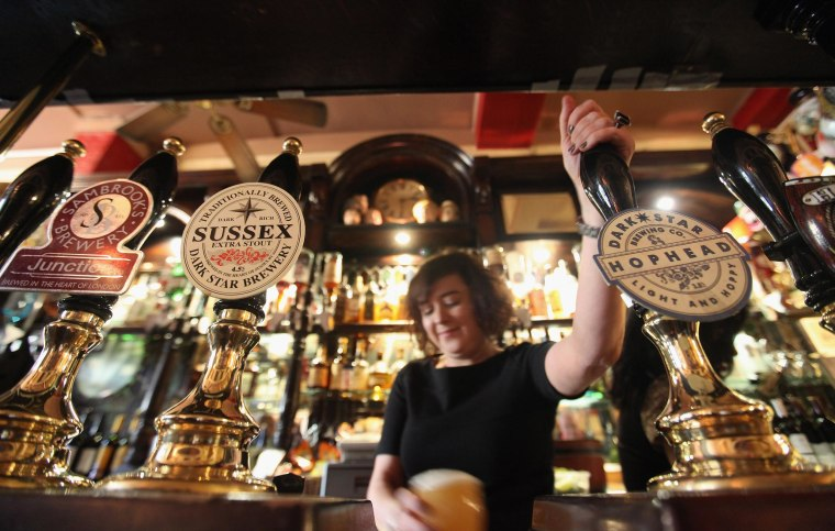 Image: A barmaid pulls a pint in The Harp pub on the day it was named as the Campaign for Real Ale's national pub of the year on Feb. 16, 2011 in London, England.