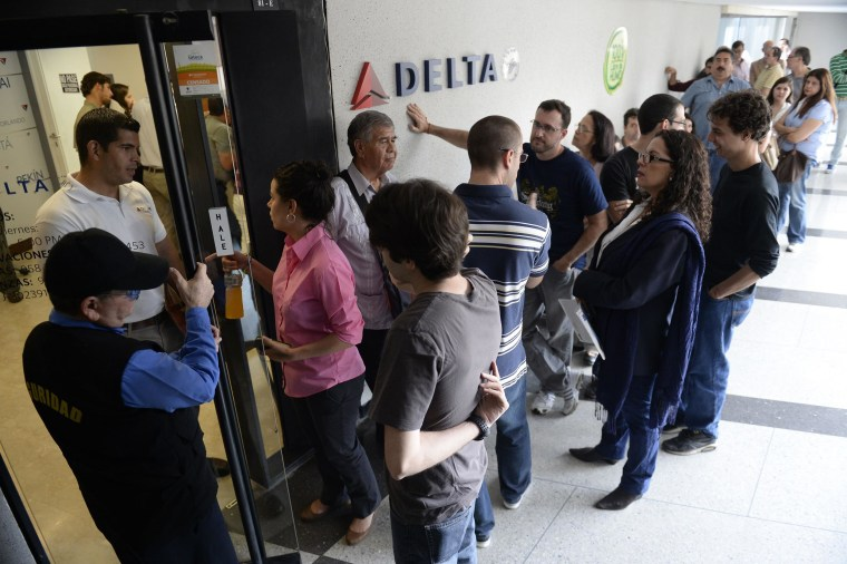 Image: People queue outside the sales office of US airline Delta, in Caracas