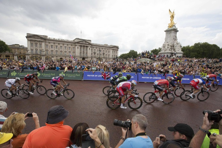 Image: The pack of riders cycles on its way past Buckingham Palace during the third 155 km stage of the Tour de France cycling race from Cambridge to London