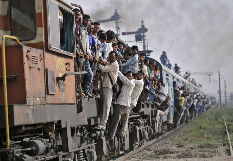 Image: Passengers travel on an overcrowded train at Loni town in Uttar Pradesh