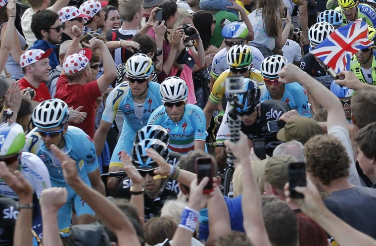 Image: Stage winner and new overall leader Italy's Vincenzo Nibali, center in blue shirt with the Italian flag on his jersey, climbs Bradfield pass during the second stage of the Tour de France