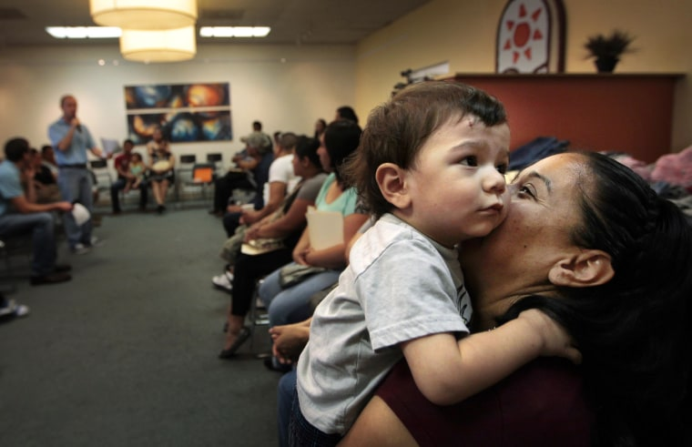 Victoria Miranda calms her 1-year-old son Anthony Miranda during a meeting at Latino Memphis in Tenn., Saturday, July 5, 2014. Hispanic students now make up one-in-five in kindergarten classrooms in 17 states.