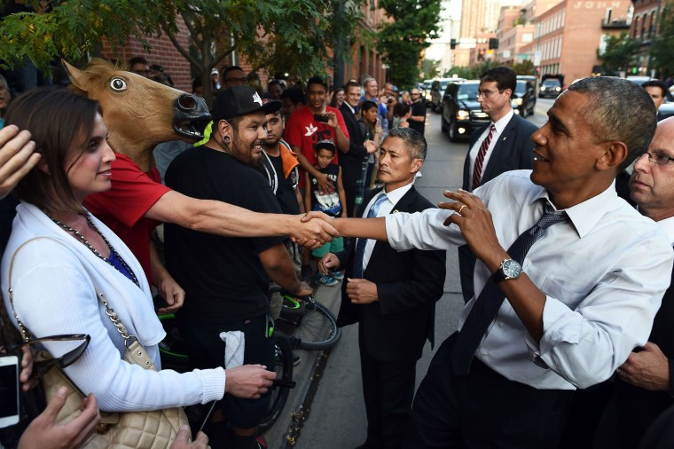 Image: President Barack Obama jokingly reacts as he shakes hands with a man wearing a horse head mask