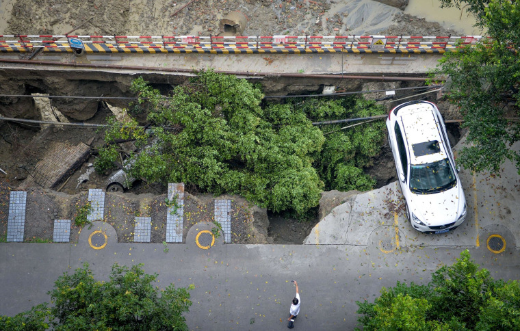Image: A man takes a photo of a collapsed parking lot