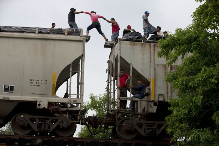 Image: A woman is helped from one boxcar to another as Central American migrants wait atop the train they were riding north, hours after it suffered a minor derailment in a remote wooded area outside Reforma de Pineda, Chiapas state, Mexico.
